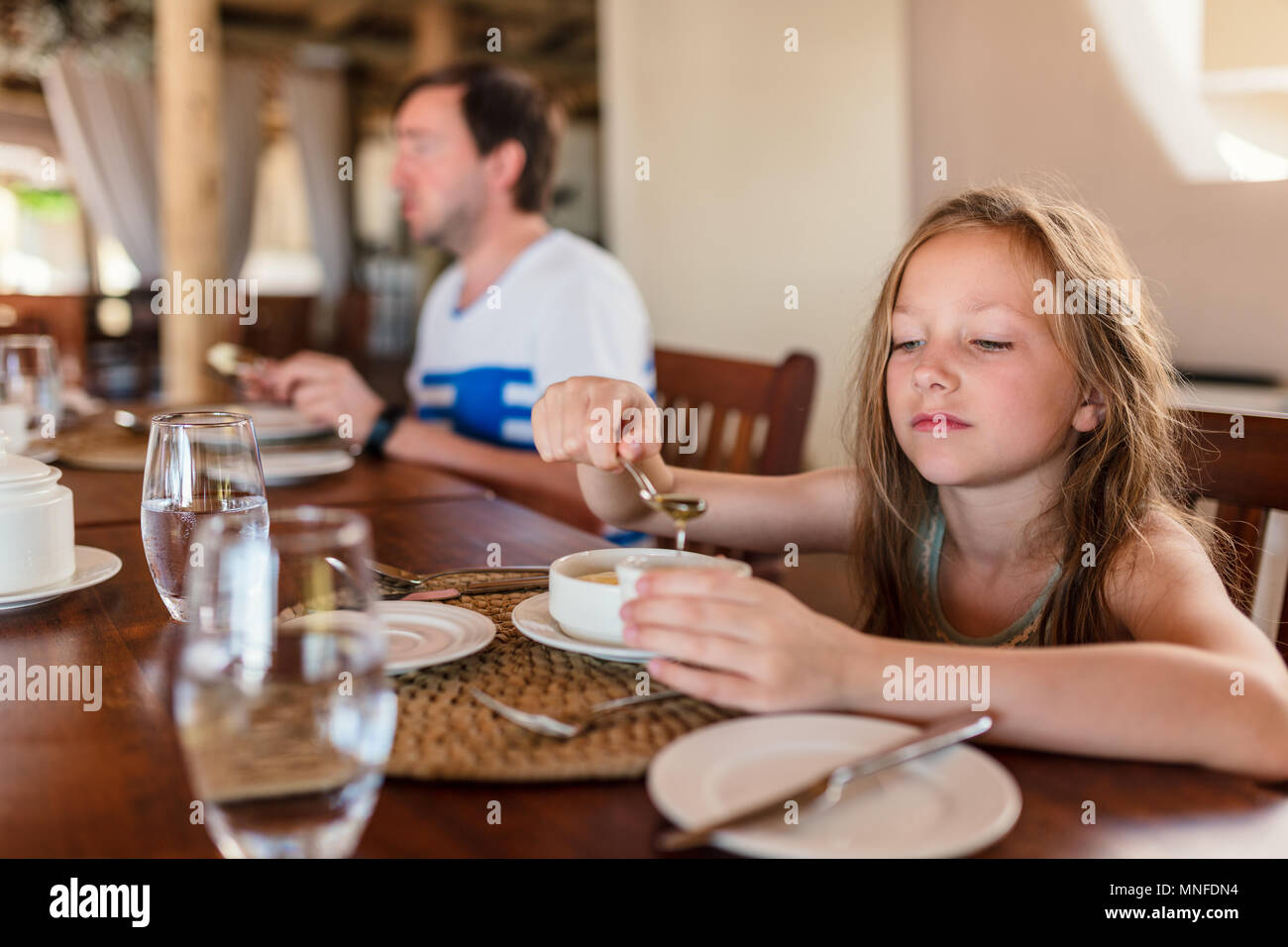 Adorable little girl eating breakfast in home or restaurant - Stock Image