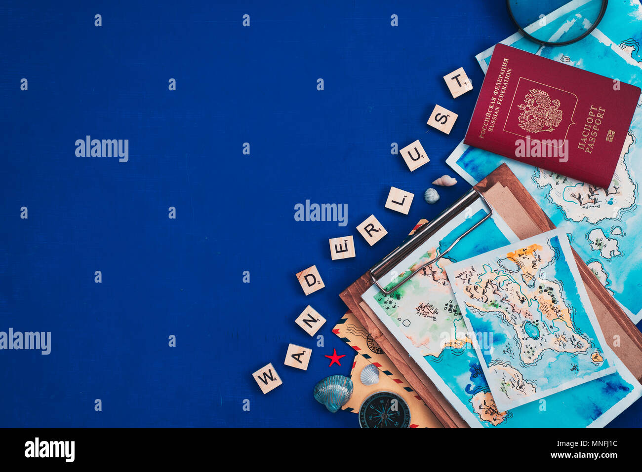 Sea travel and exploration concept. Watercolor maps, passport, compass, post envelopes, and Wanderlust wooden letters flat lay on a navy blue backgrou - Stock Image