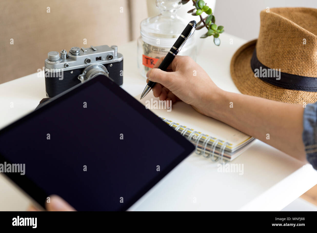 Travel planning concept on table. Traveler's accessories and items with notebook and money saving jar, sunglasses and hat Stock Photo