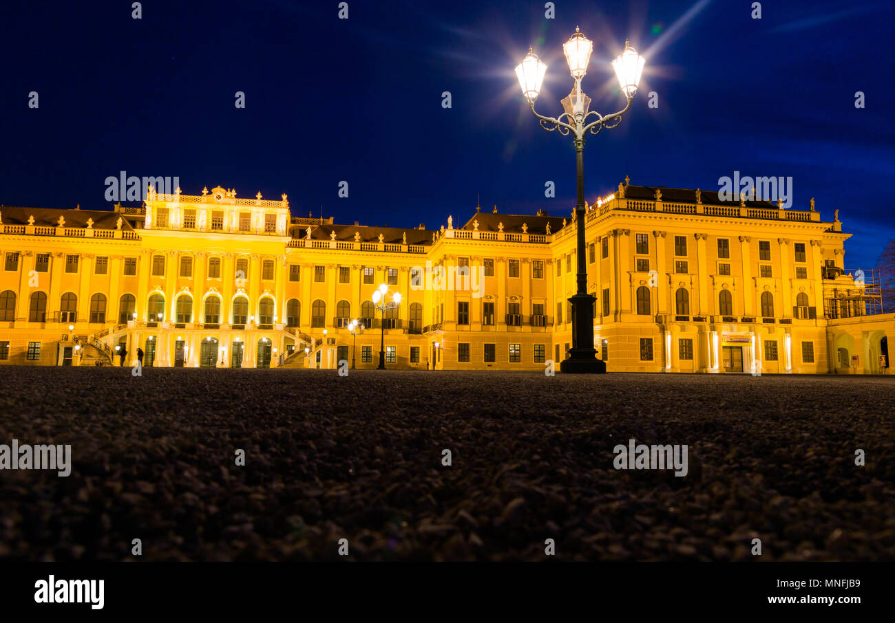 Schönbrunn Palace at night in gold light illumination. Low, wide angle perspective. Vienna, Austria, 25 March 2017 - Stock Image