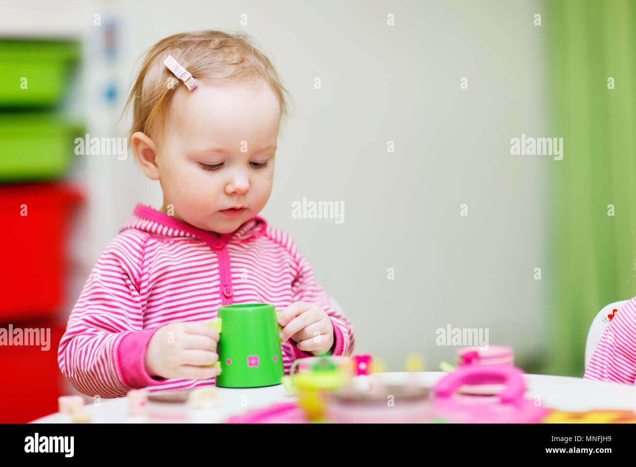 Adorable toddler girl playing with toys at home or daycare place Stock Photo