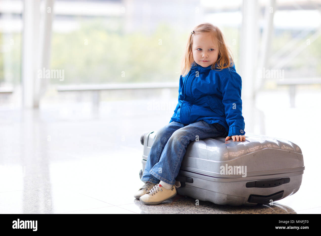 Adorable little girl at airport sitting on suitcase Stock Photo