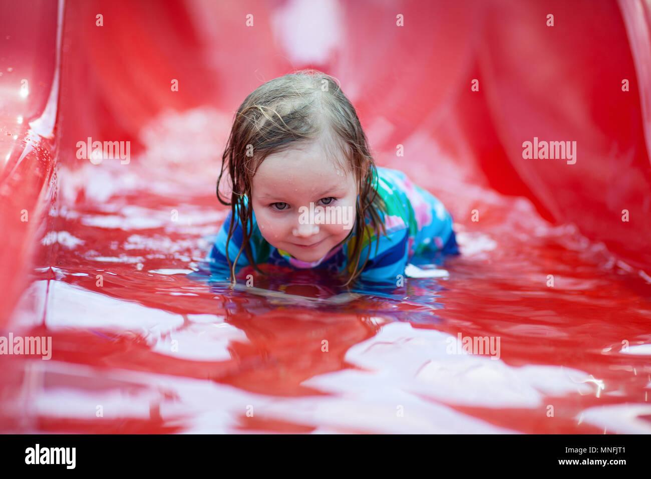 Portrait of little girl on water slide at aquapark - Stock Image