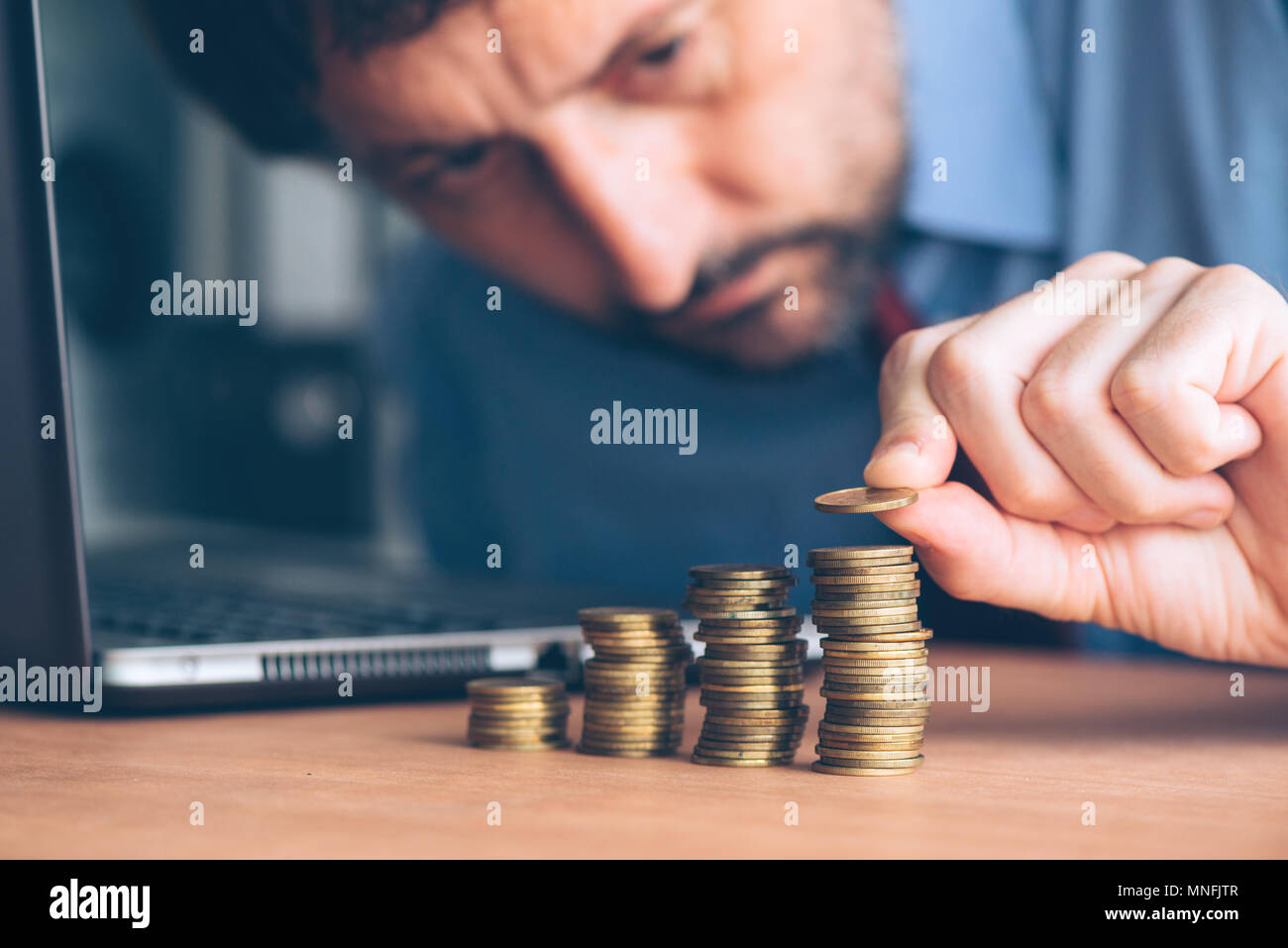 Finances and budgeting, careful businessman stacking coins on office desk - Stock Image