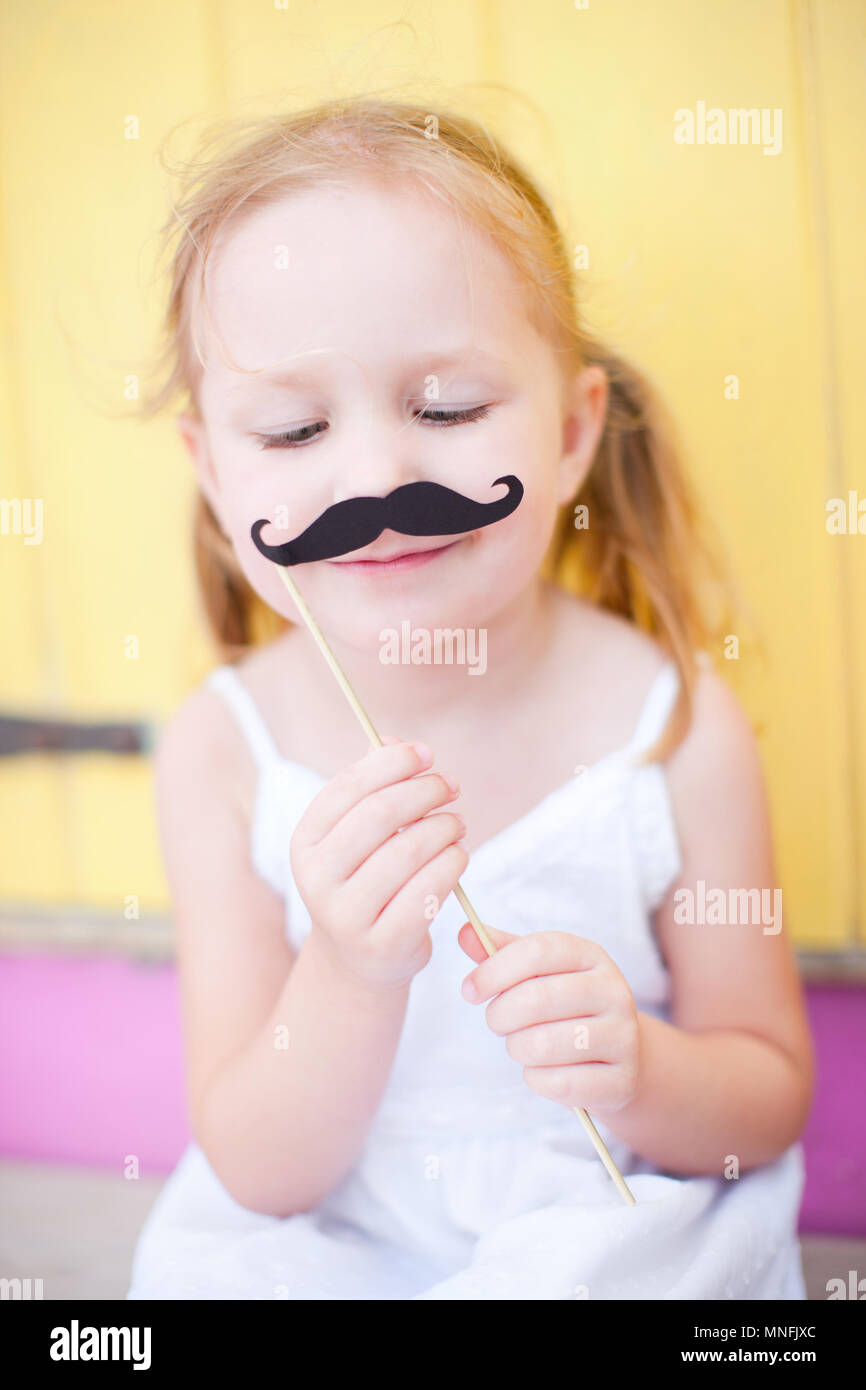 Adorable little girl holding mustache party accessory - Stock Image