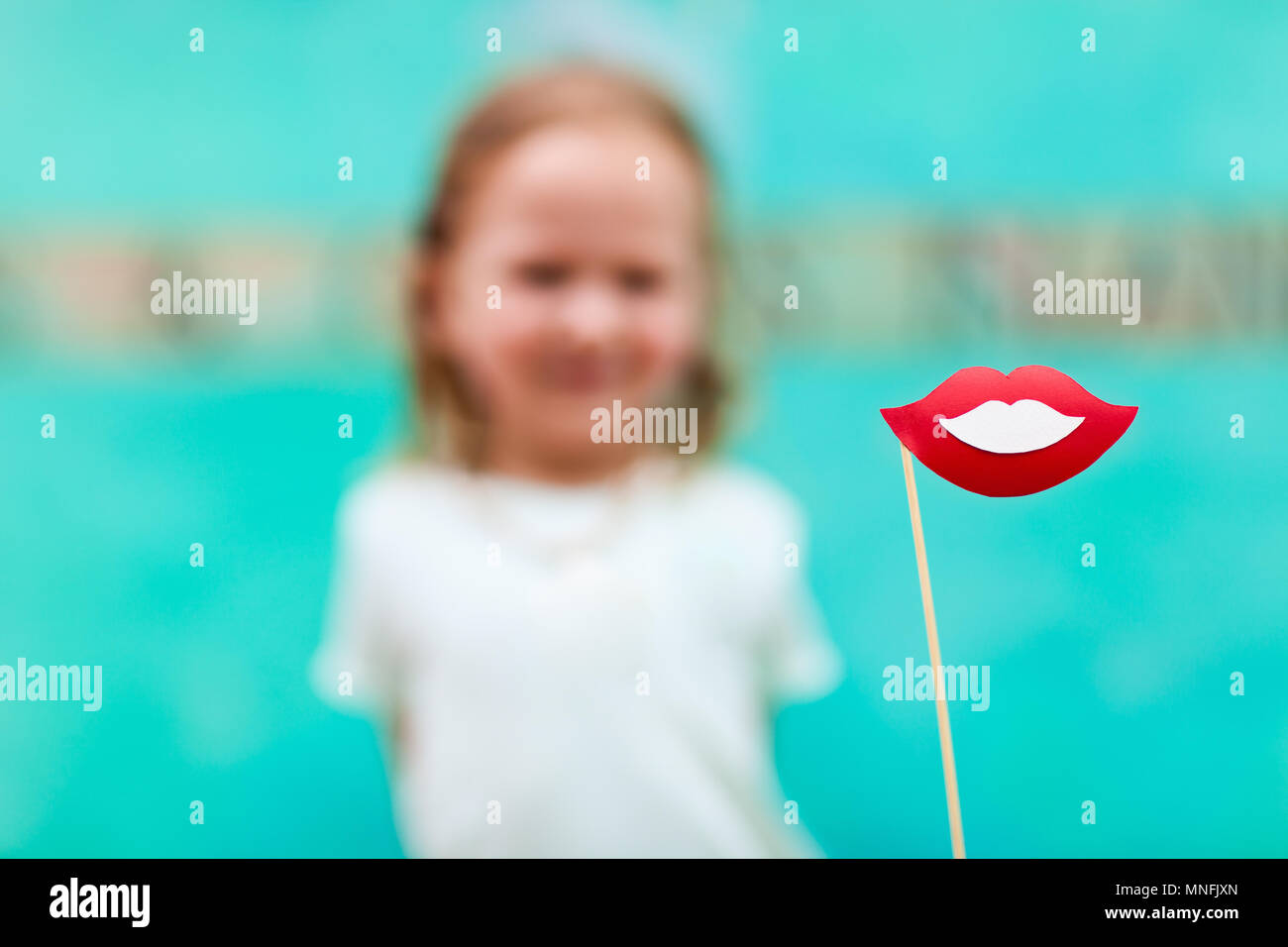 Adorable little girl holding lips party accessory - Stock Image