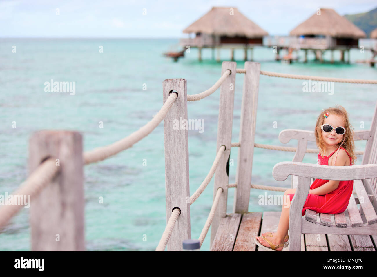 Little girl at terrace of over water bungalow - Stock Image