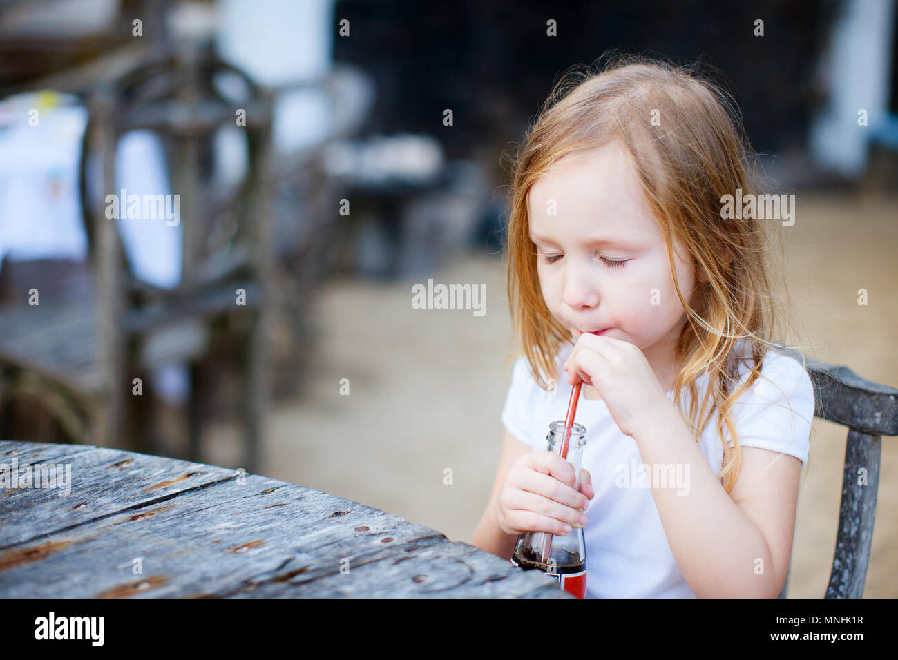 Adorable little girl drinking with a straw a soft drink - Stock Image