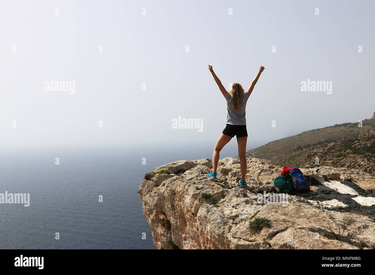 Triumphant young woman arms raised celebrates after a successfully climb. Standing back to camera looking out at sea from the cliff edge. Copy space. - Stock Image