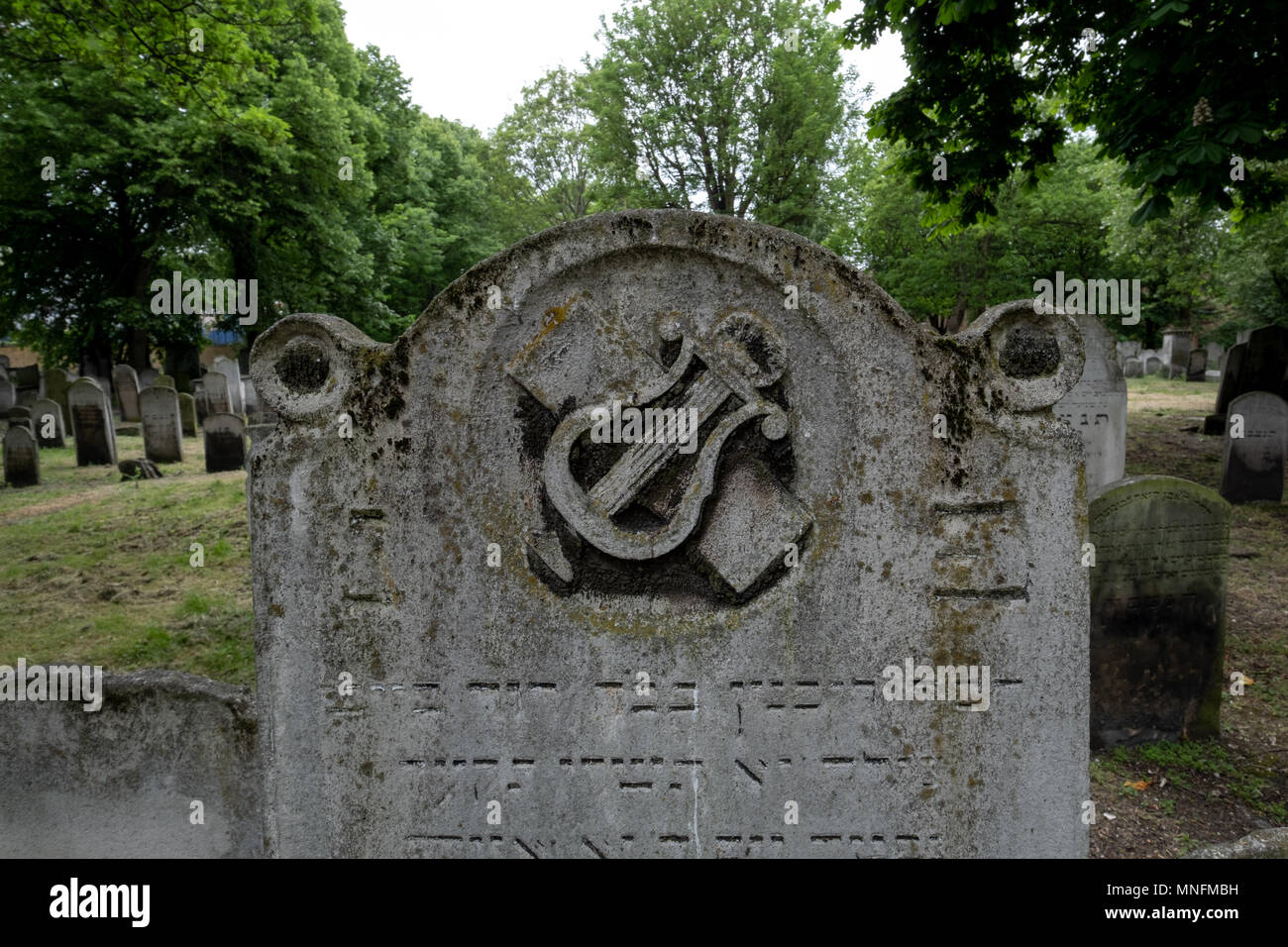 London UK. Close up photo of tombstone at the historic Jewish cemetery at Brady Street, Whitechapel, East London, showing lyre / harp symbol. - Stock Image