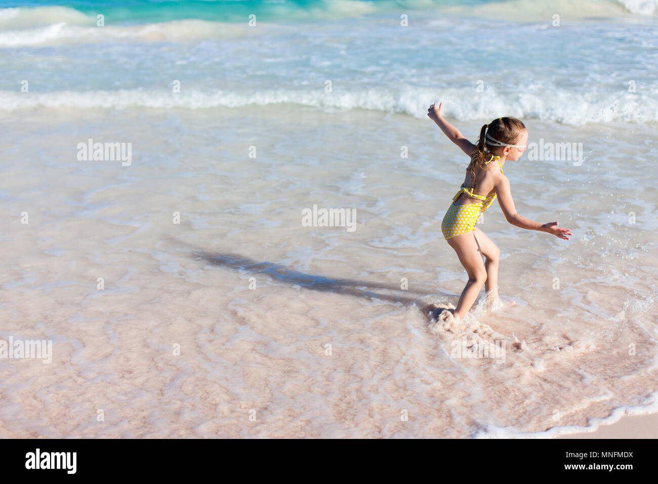 Adorable little girl in yellow swimsuit having fun at beach during summer vacation - Stock Image