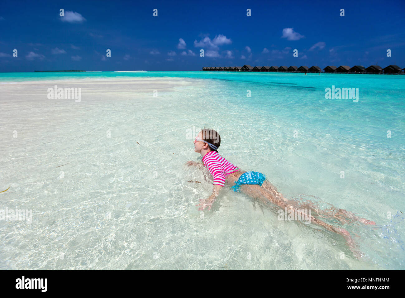 Little girl in a colorful sun protection swimwear on vacation swimming in a shallow water at tropical lagoon - Stock Image