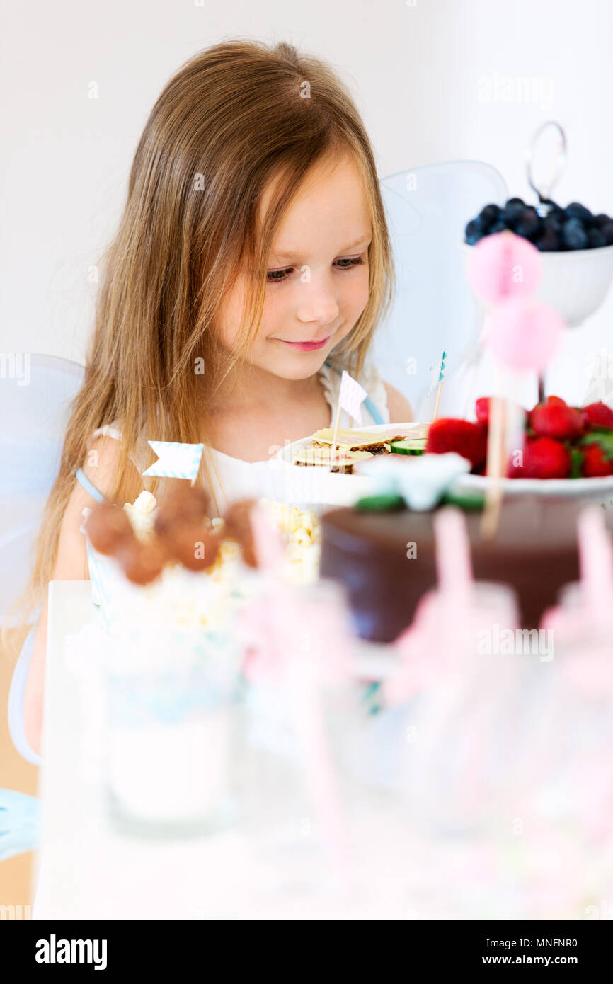 Adorable little fairy girl on a birthday party in front of dessert table - Stock Image