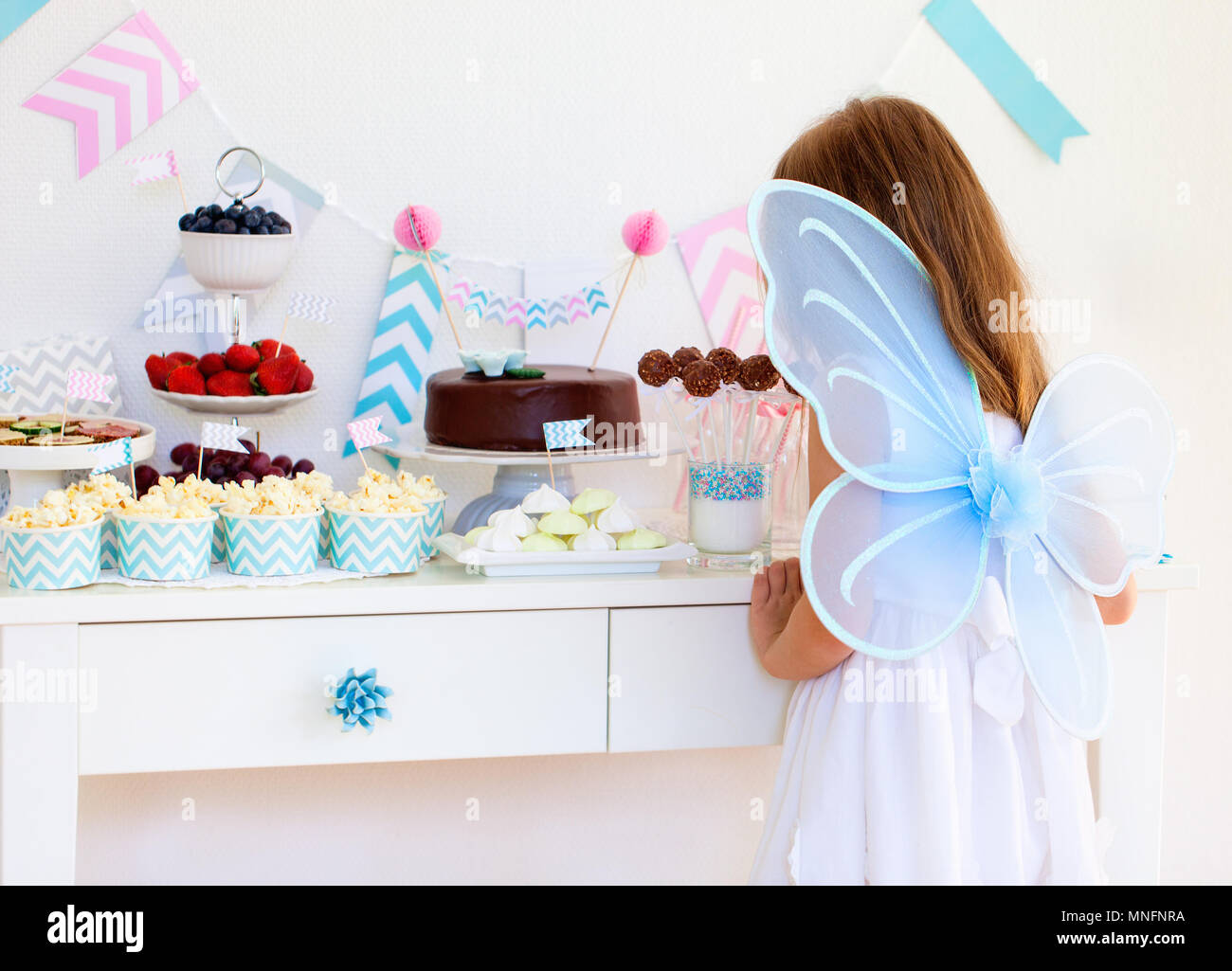 Adorable little fairy girl with wings on a birthday party near dessert table - Stock Image