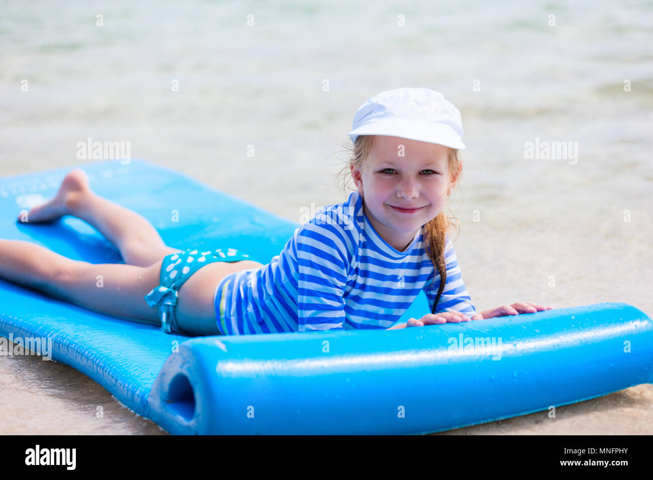 Little girl in a colorful sun protection swimwear on vacation swimming on floating mat in a shallow water at tropical lagoon - Stock Image