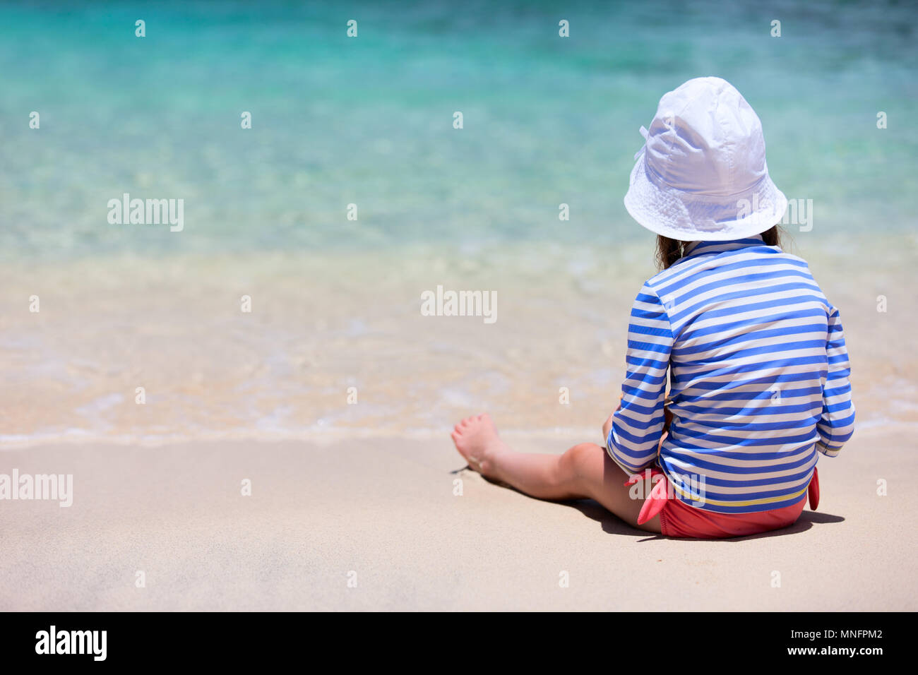 Little girl in a colorful sun protection swimwear on vacation sitting at tropical beach - Stock Image