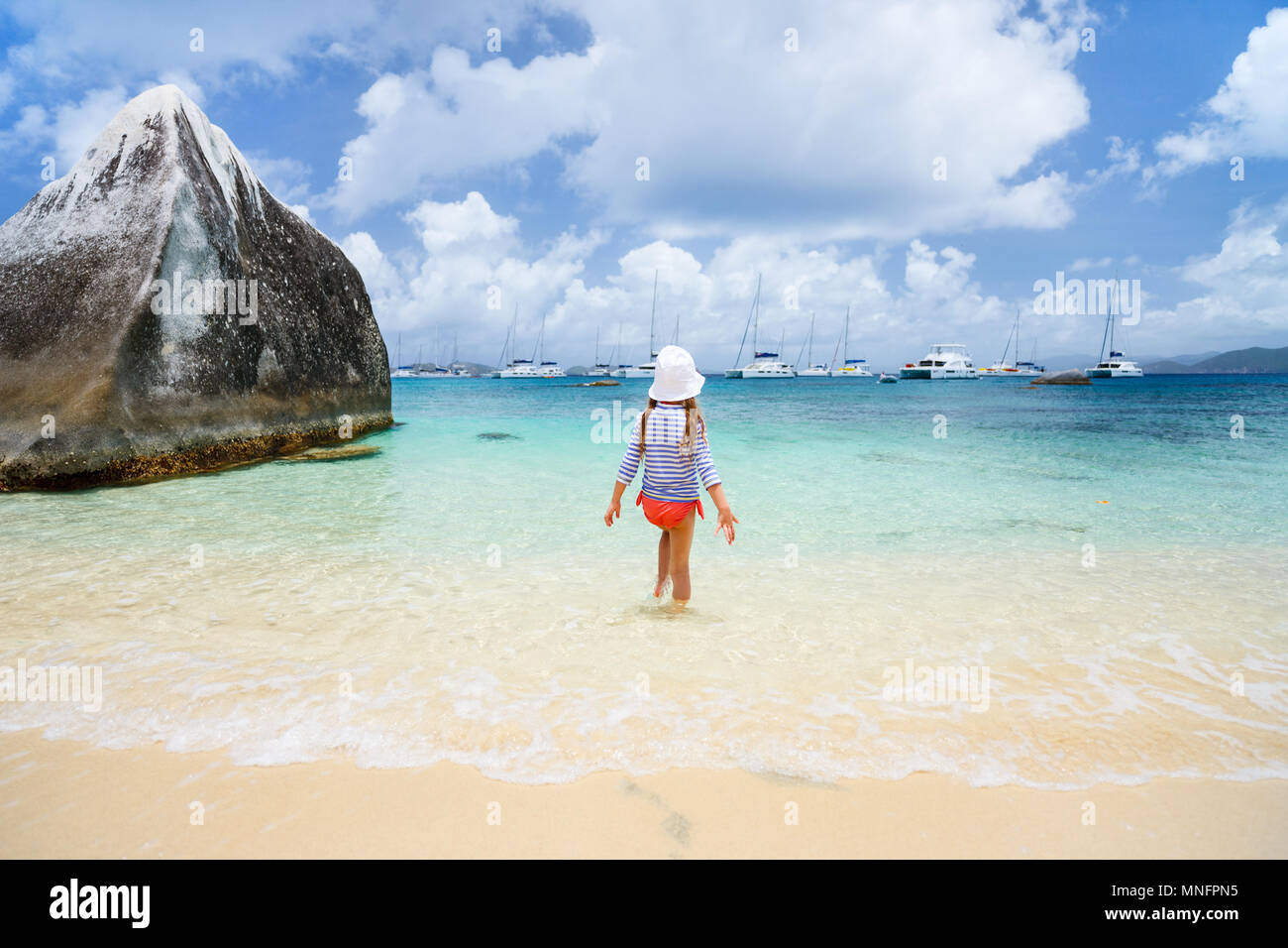 Little girl in a colorful sun protection swimwear on vacation at tropical beach - Stock Image