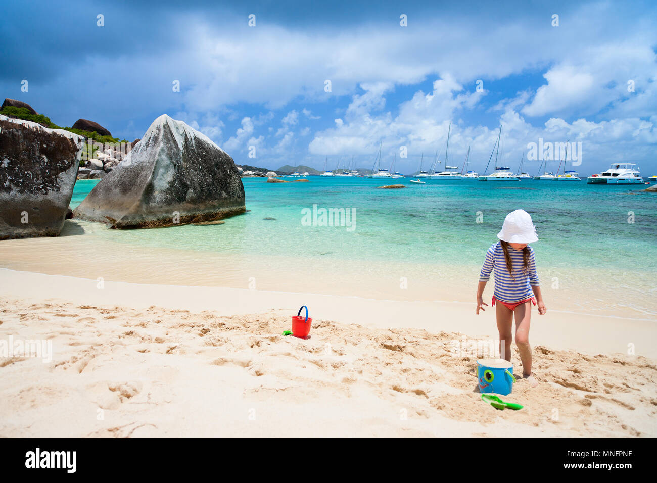 Adorable little girl wearing rash guard for sun protection at beach during summer vacation - Stock Image