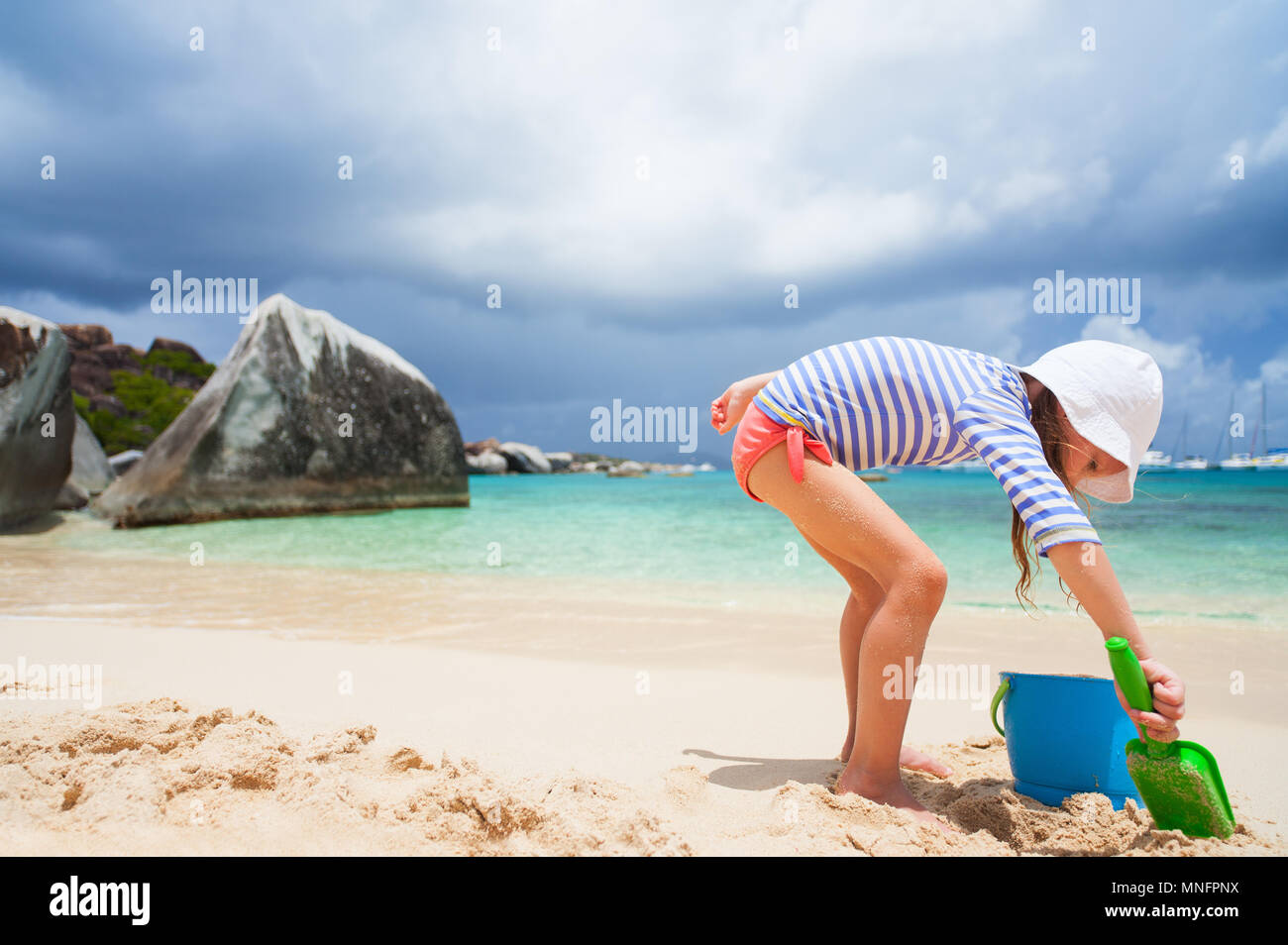Adorable little girl wearing sun protection rash guard at beach during summer vacation - Stock Image
