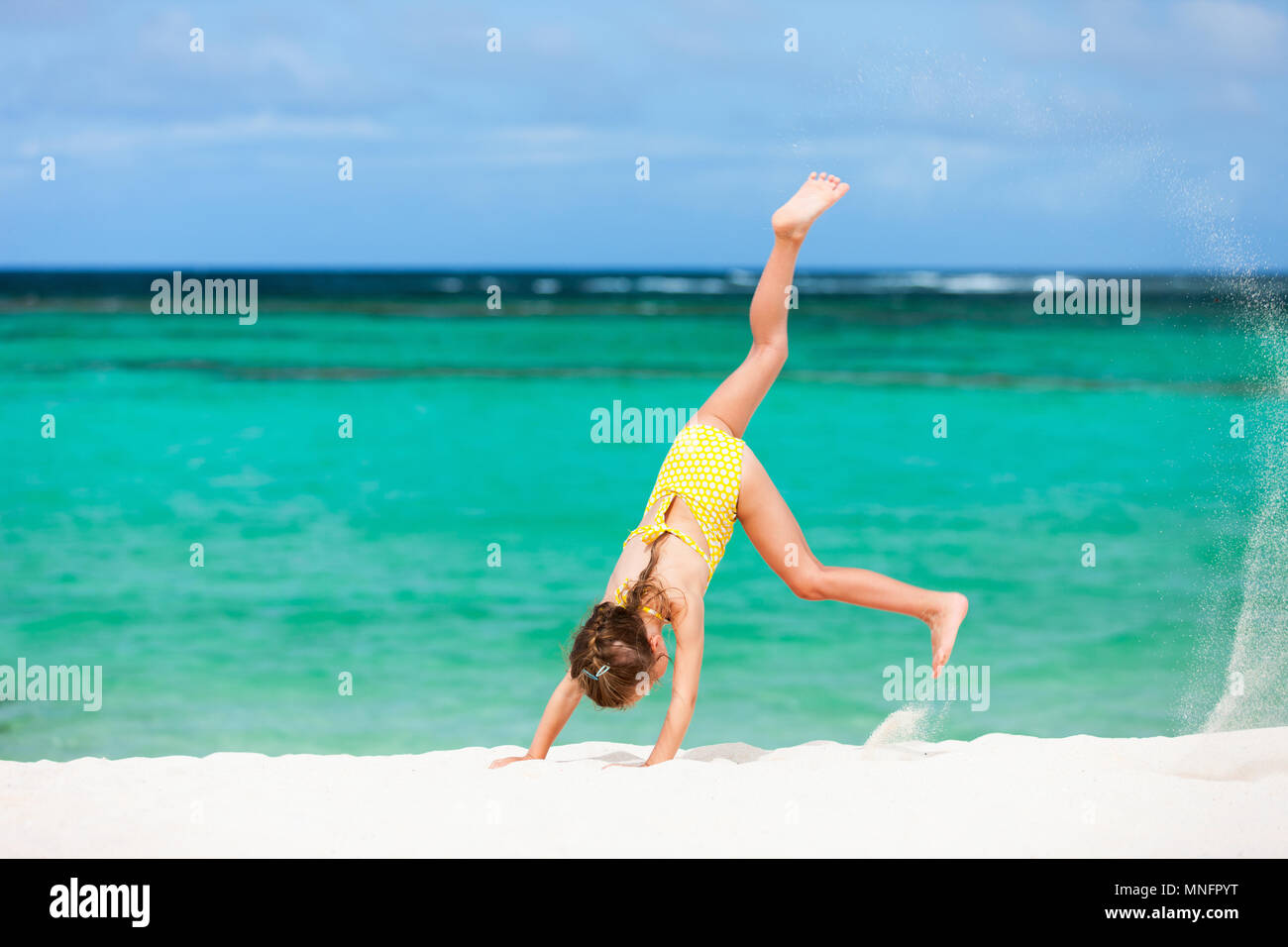 Cute little girl having fun making cartwheel and enjoying vacation on tropical beach with white sand and turquoise ocean water - Stock Image