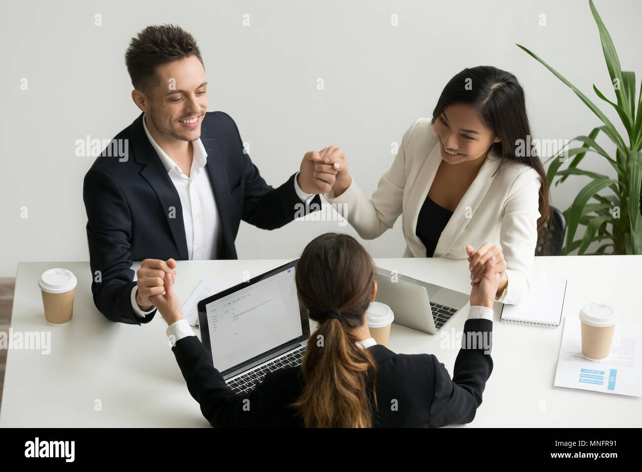 Business team meditating together holding hands - Stock Image