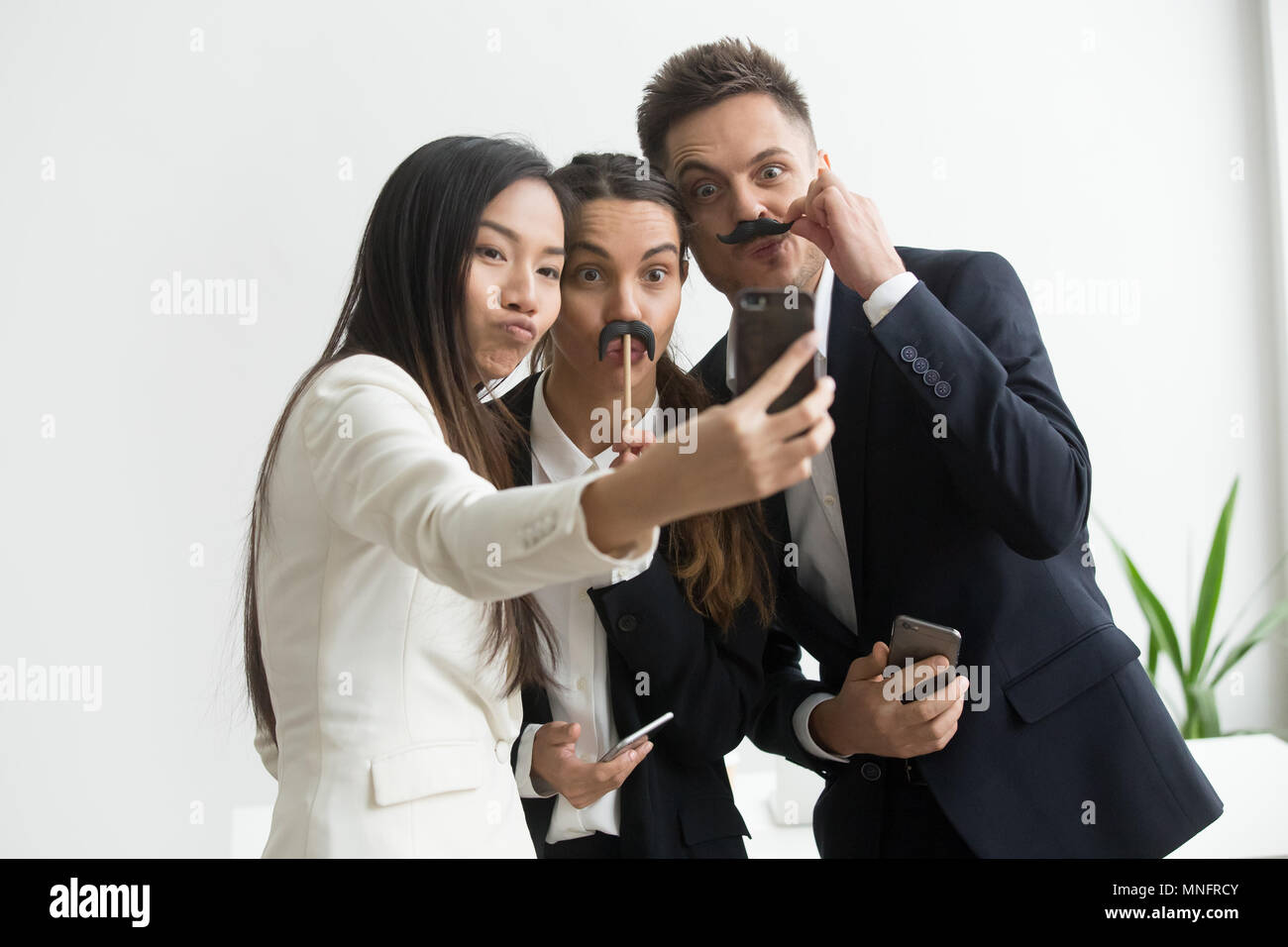 Coworkers making picture with mustache accessory - Stock Image