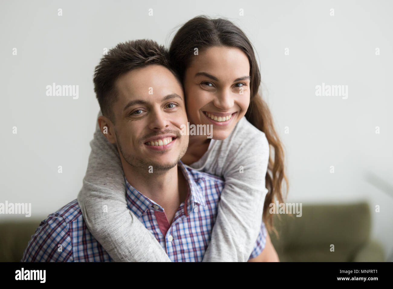 Smiling man piggyback cheerful wife looking at camera - Stock Image