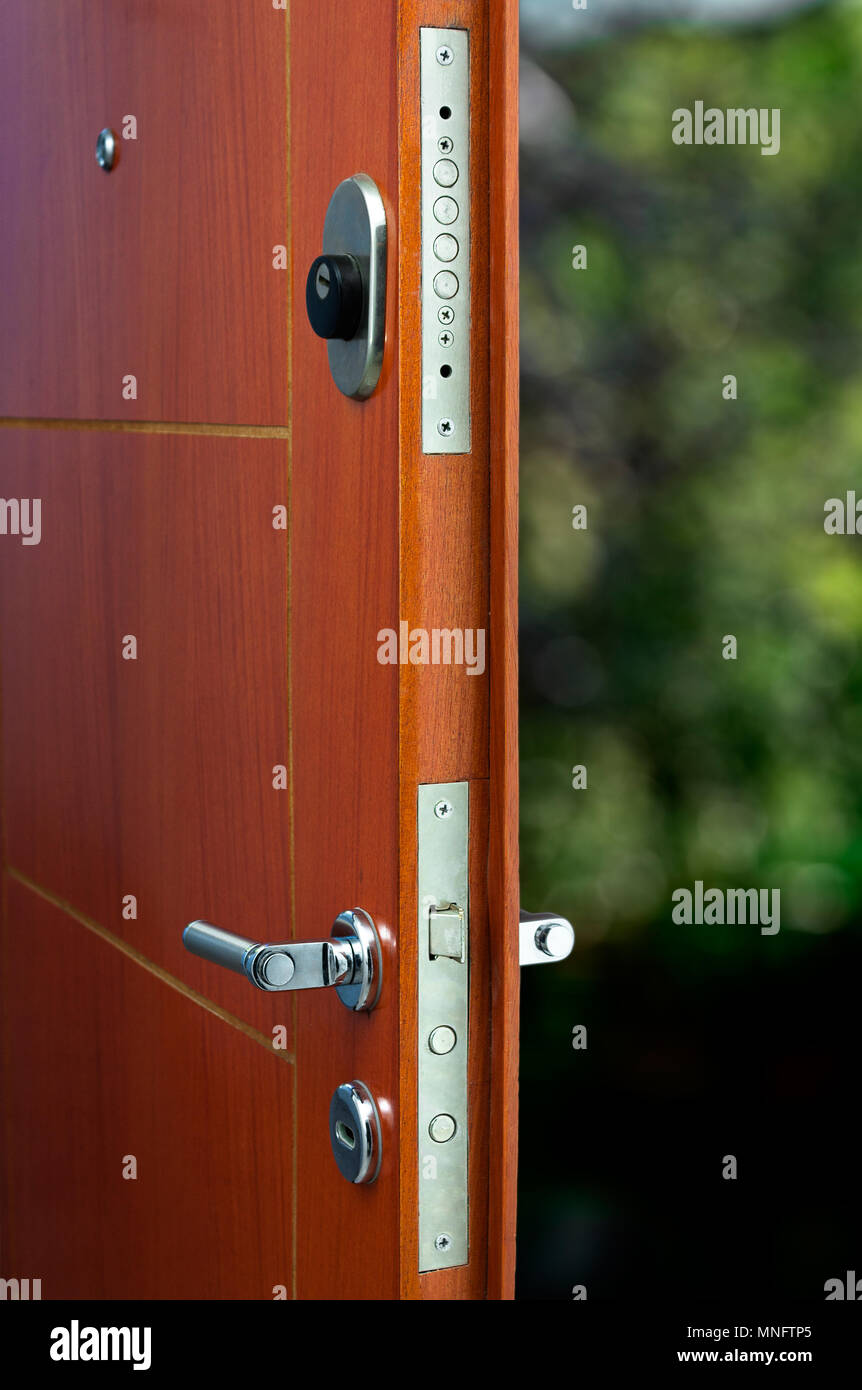 Open door of a family home. Close-up of the lock an armored door. - Stock Image