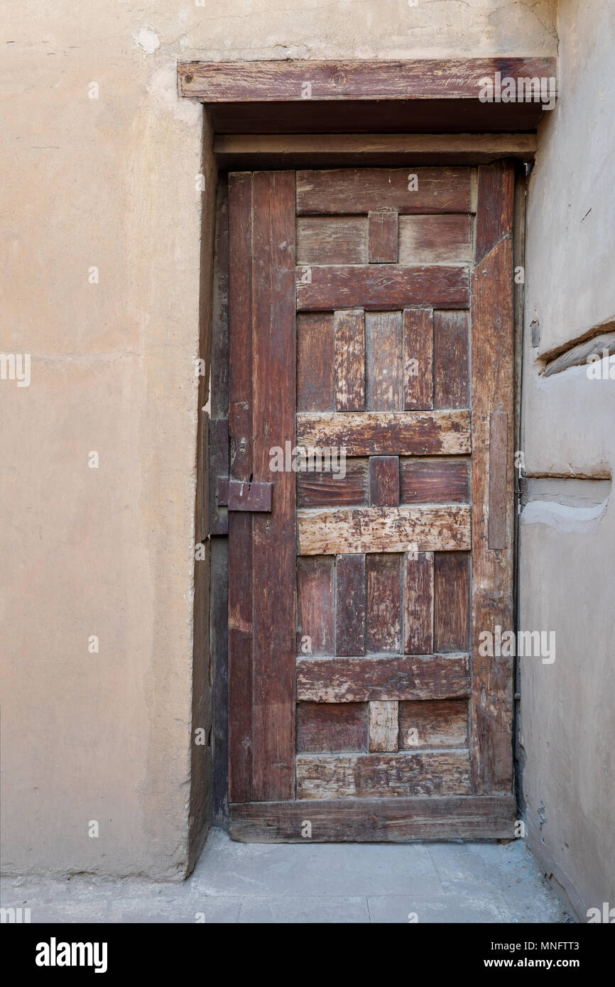 Wooden aged decorated door and stone wall, Medieval Cairo, Egypt - Stock Image