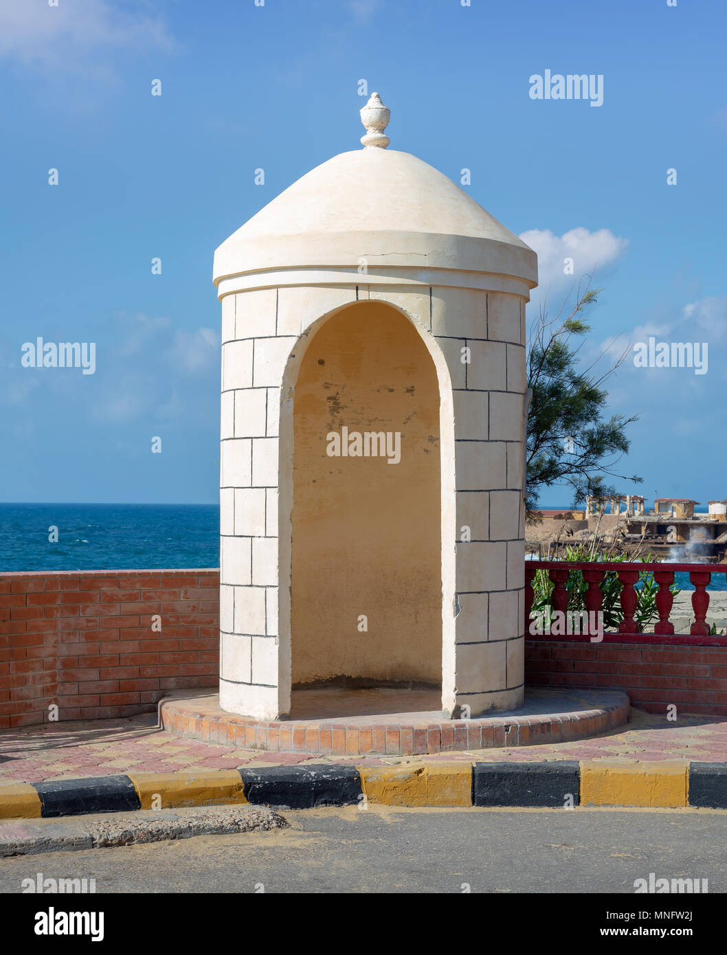 Old guard booth of white bricks with Mediterranean Sea, clear sky, and tree in the background located at Montaza public park, Alexandria, Egypt - Stock Image