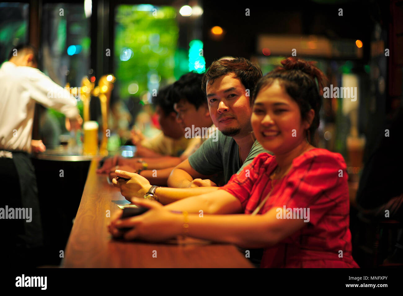 Friends waiting at bar for their beers, Hops Brew House Pattaya Thailand - Stock Image