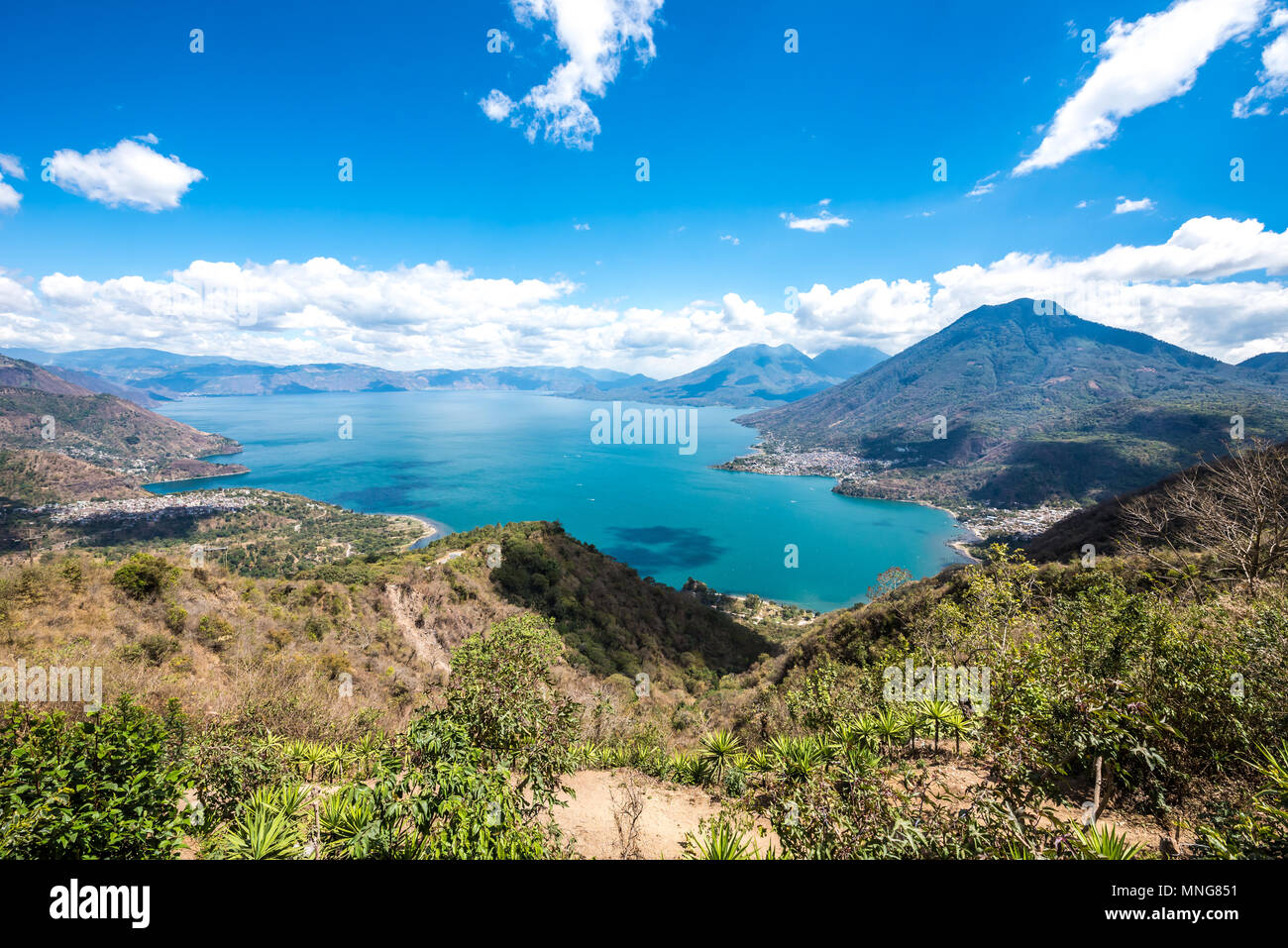 Panorama view to the lake Atitlan with volcanos - small villages San Pedro, San Marcos, San Juan and Panajachel at lake Atitlan in the highland of Gua - Stock Image