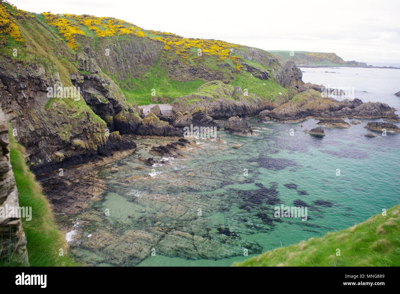 Inviting Turquoise Water of the Rugged Coast by Findlater Castle, Sandend, Scotland, UK. - Stock Image