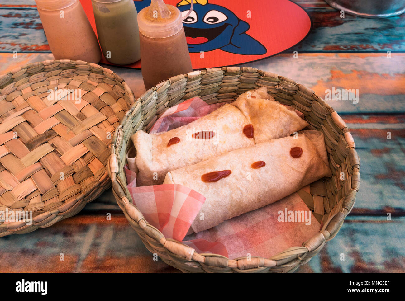 Basket with two shrimp burritos on a table at Baja Fish Taquito in San Miguel de Allende, Mexico - Stock Image