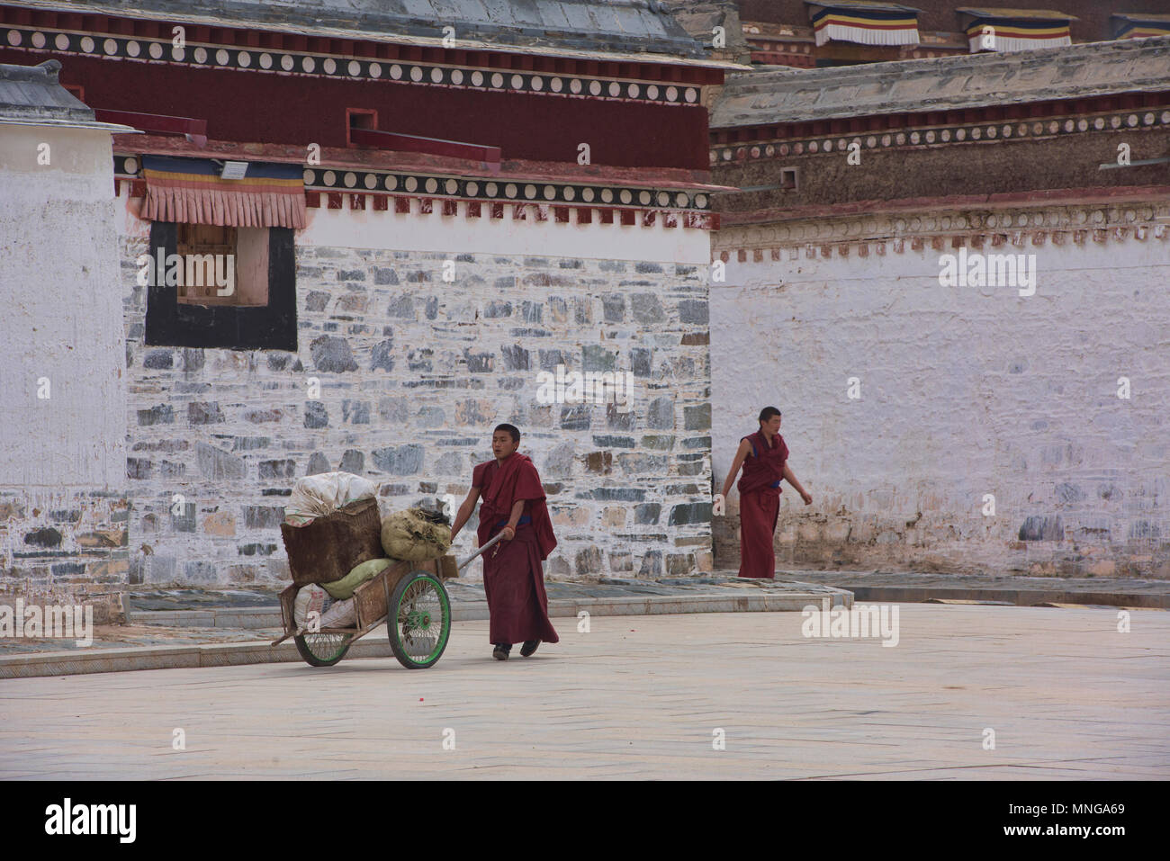 Gelukpa monks doing chores, Labrang Monastery, Xiahe, Gansu, China - Stock Image