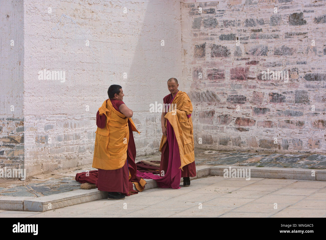 Gelukpa monks putting on their robes, Labrang Monastery, Xiahe, Gansu, China - Stock Image