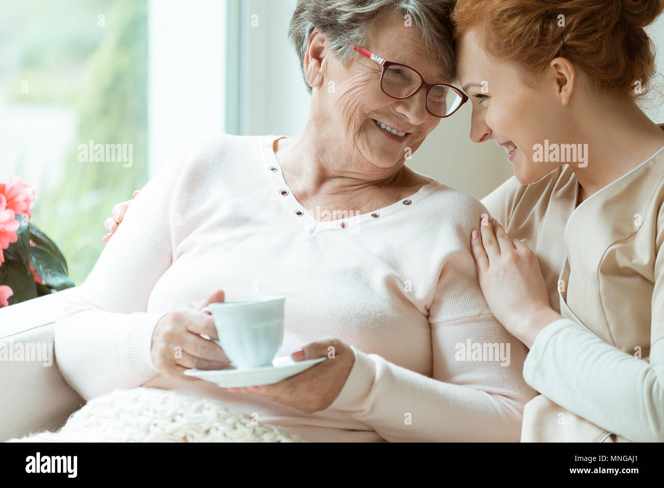 Elder woman with cup of tea and her friendly caretaker looking in each other's eyes - Stock Image