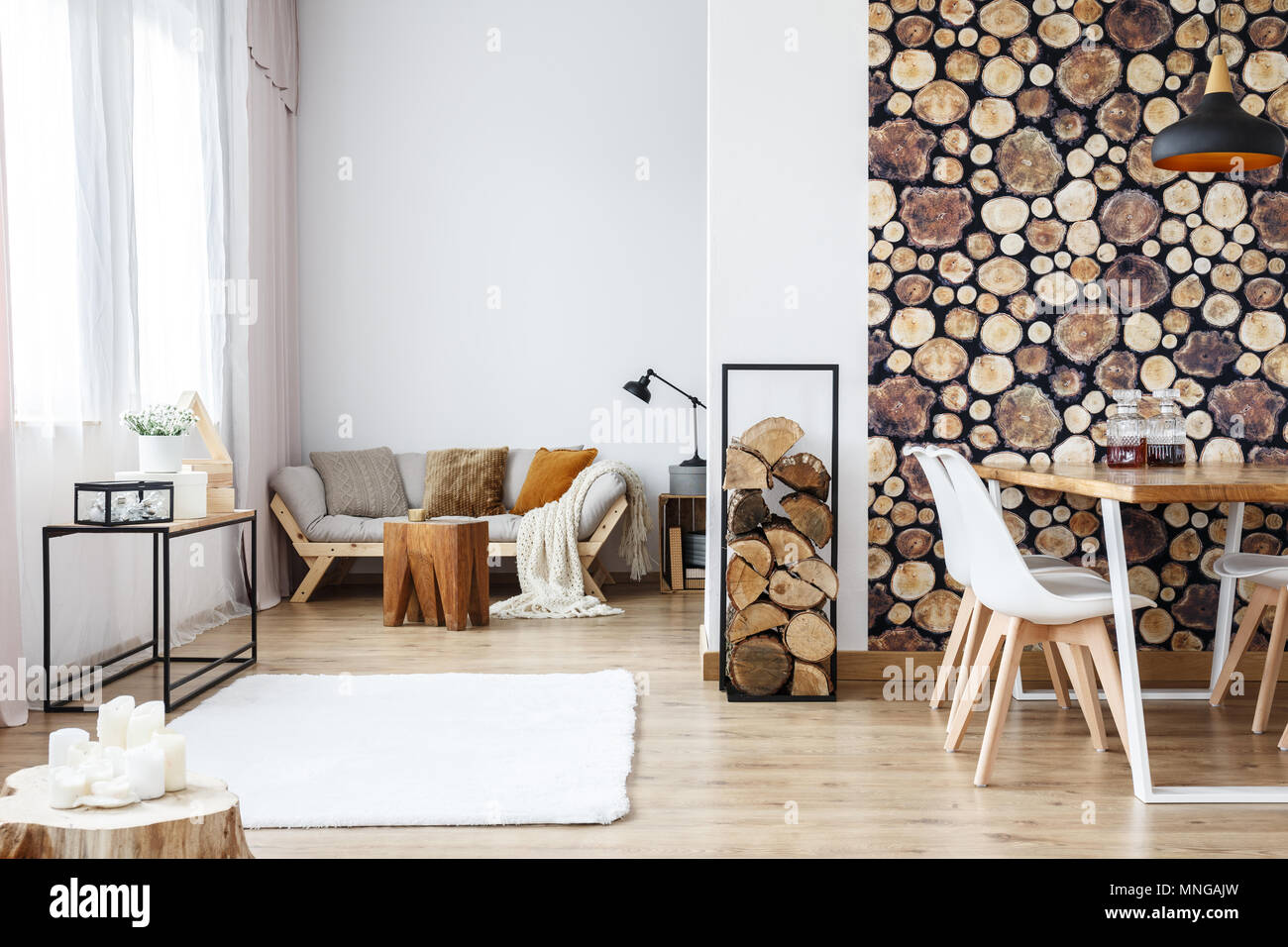 Wooden log texture wallpaper in cozy dining space of white open plan apartment with sofa, rug and tree stump accessories - Stock Image