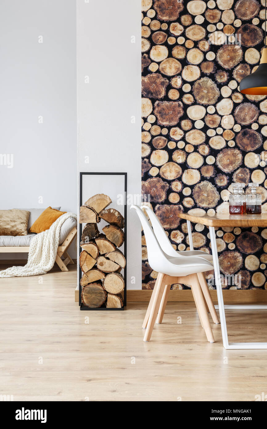 Warm dining room decor inspired by autumn woodland with simple furniture, firewood and logs wallpaper - Stock Image