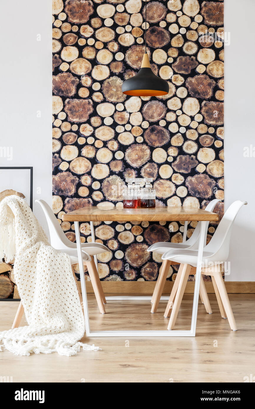 Soft textiles and log wallpaper in impressive dining room with scandinavian decor, white chairs and wooden communal table - Stock Image