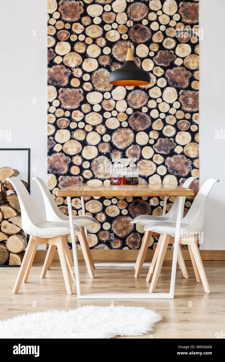 Wooden design details in warm winter interior of dining room with white wall, communal table and wine decanters - Stock Image