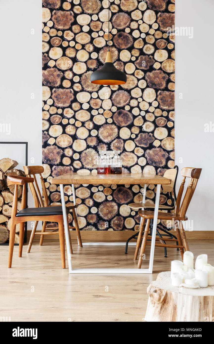 Rustic home decor of dining space in loft interior with wooden table and log wallpaper - Stock Image