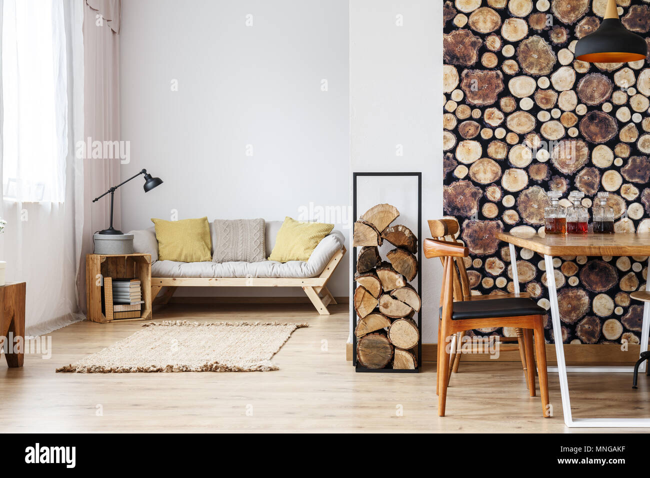 Natural design in open plan studio with log holder, wood wallpaper in separated dining room and wooden box standing next to sofa in living space - Stock Image