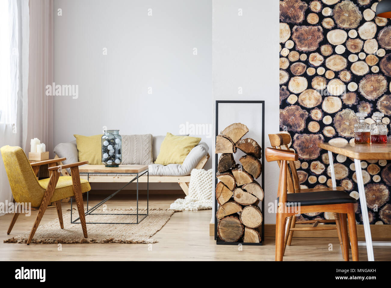 Designer armchair, sofa, firewood and coffee table in warm cozy apartment with open dining area and log pile wallpaper - Stock Image