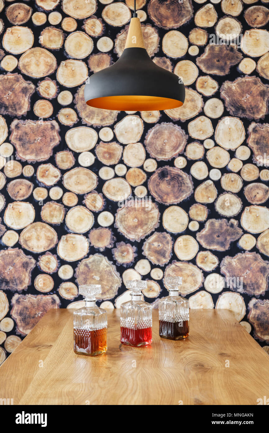 Glass decanters placed on wooden table in interior with stylish lamp and wooden log wallpaper - Stock Image