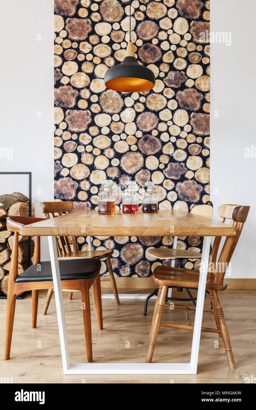 Wooden dining table, chairs and wall decoration in modern bright dining room with natural design - Stock Image