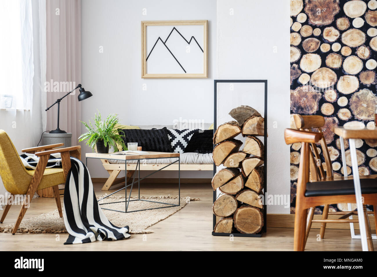 Cozy winter interior design for minimalist with wooden accessories, warm colors and fire logs - Stock Image