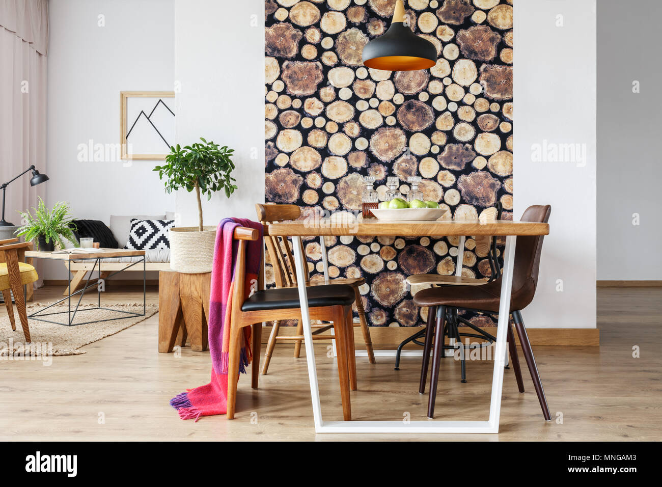 Cozy rustic design of spacious warm loft interior with wooden log wallpaper and natural tree stump - Stock Image