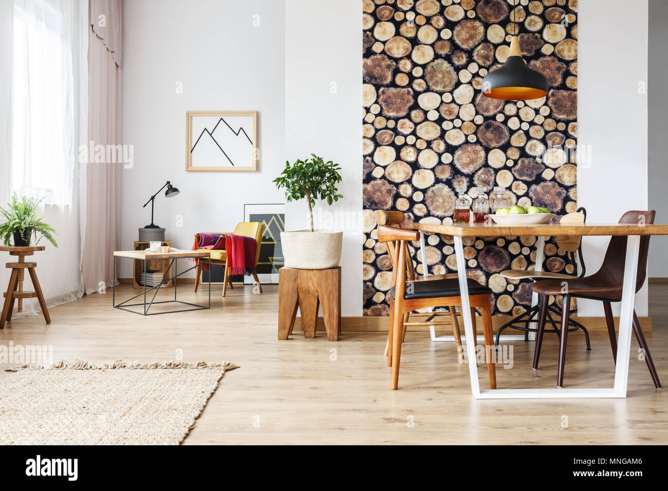 Dining table and rustic brown chairs in contemporary spacious flat with wooden accents - Stock Image