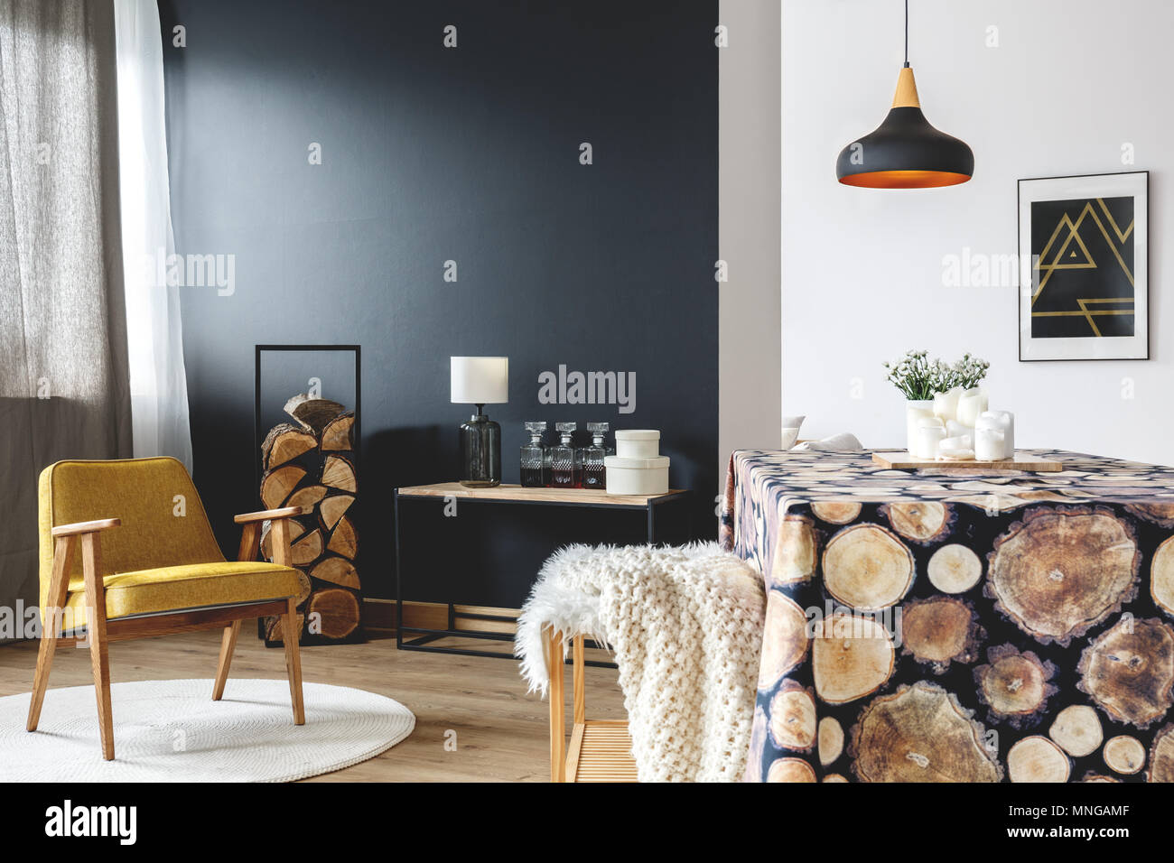 Yellow armchair, logs and cozy wood decor theme in natural apartment with dining space - Stock Image